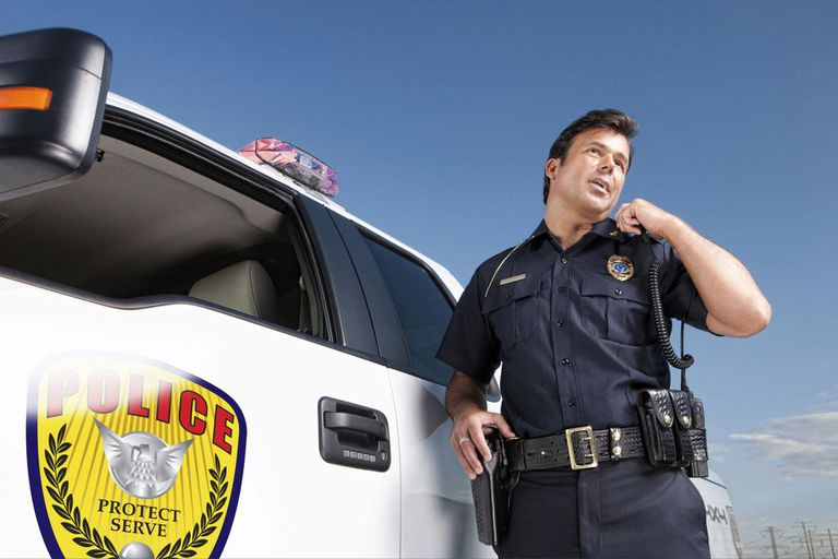 A mid adult male law enforcement officer stands outside his patrol vehicle, talking into his shoulder mounted walkie talkie, communicating with dispatch or another officer.