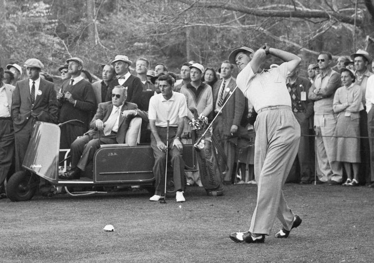 As Bobby Jones (in the golf cart) looks, on Dr. Cary Middlecoff of Kiamesha Lake, N.Y., drives off from the 14th tee in the second round of the 1955 Masters Golf Tournament.