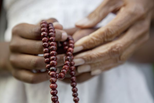 Close up of a child holding mala or prayer beads