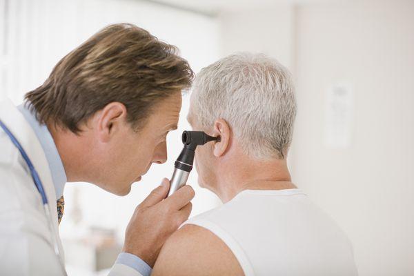 Doctor examining patients ear in doctors office
