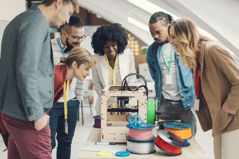 Group of people watching 3D printer