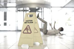 Businessman slipping on wet office floor