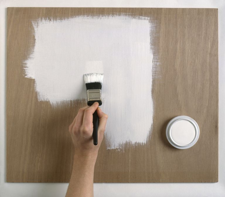 Applying a coat of gesso primer on wooden surface, close-up