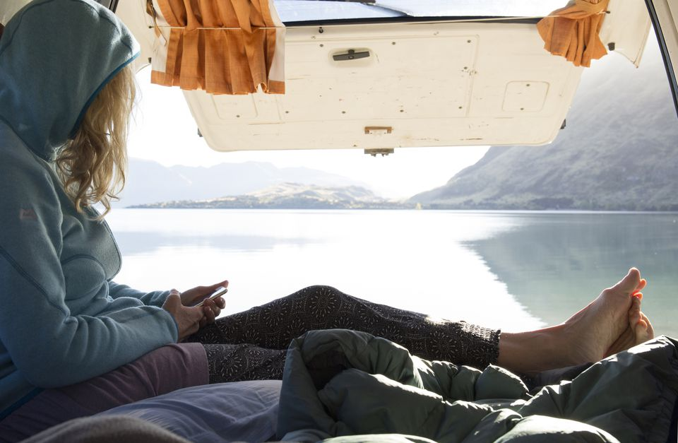 Woman relaxes in camper van, texting, mountain lake