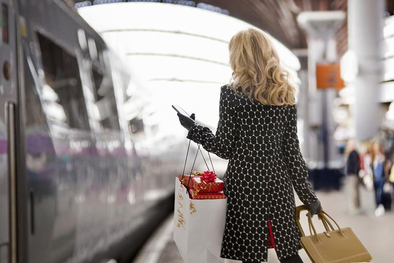 Female rail traveller in the holiday season texting home.
