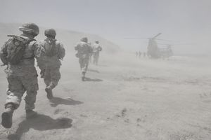 Marines move through a dust cloud toward a CH-46 Sea Knight.