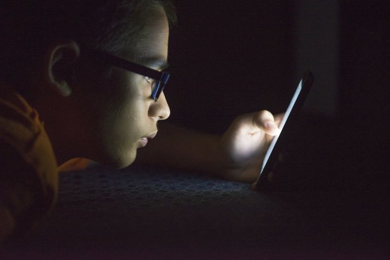 Teenager looking at cell phone in dark