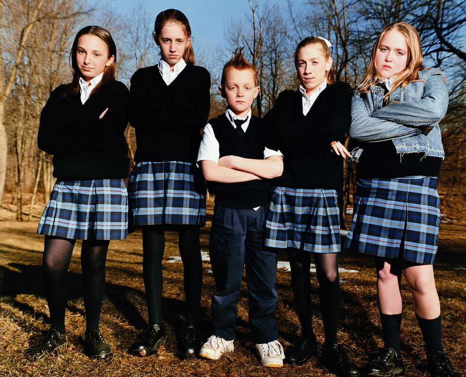 Five schoolchildren (8-13) standing with arms crossed, portrait