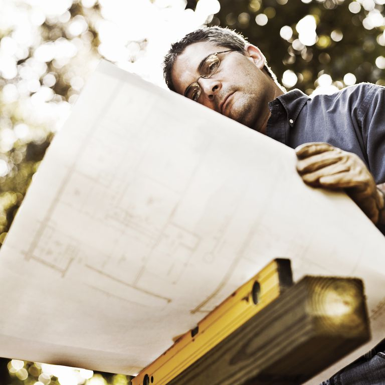 Carpenter looking at plans, outdoors, low angle view