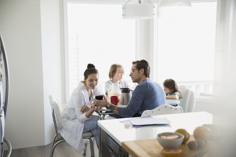 Family in pajamas enjoying breakfast with parents texting