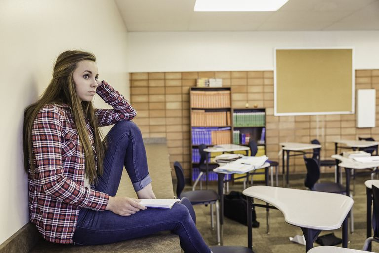 Worried teenage girl sitting in a classroom