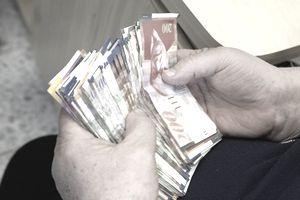 Israeli shekels in hands of moneychanger, Akko, Israel