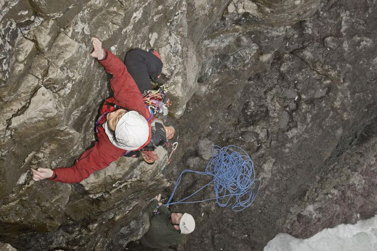 Climber scaling rocky cliff face