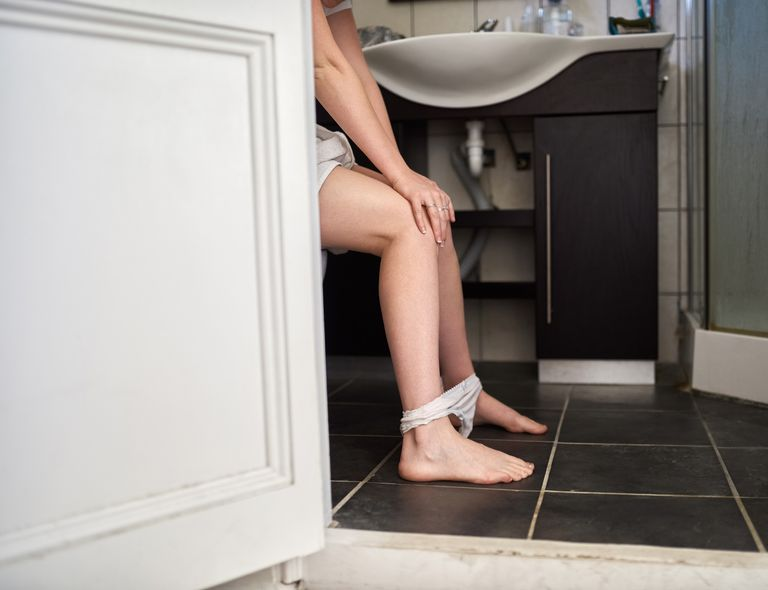 woman in bathroom with panties around ankles