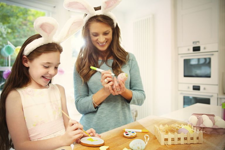 Mother and daughter wearing costume rabbit ears coloring Easter eggs and cookies
