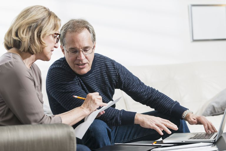mature couple talking and writing
