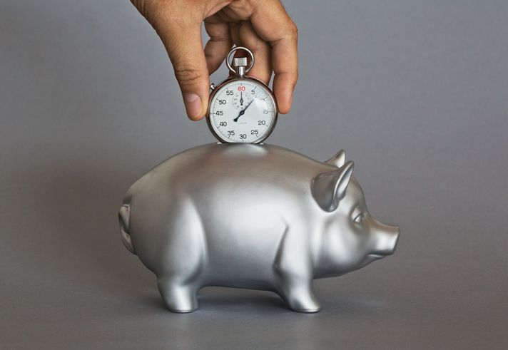 time saving photo illustration depositing stopwatch into piggy bank