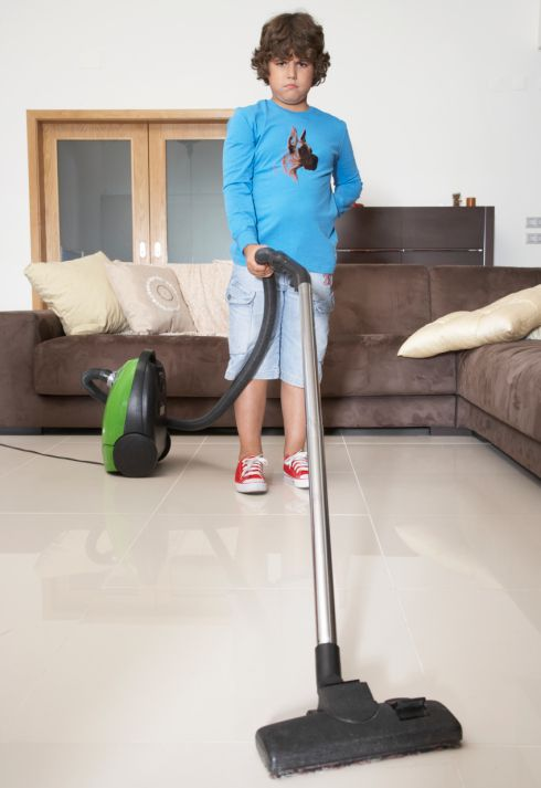 Boy using vacuum cleaner in living room