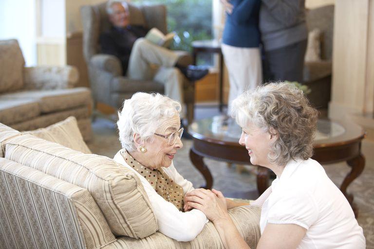 Nurse comforting senior woman in retirement home