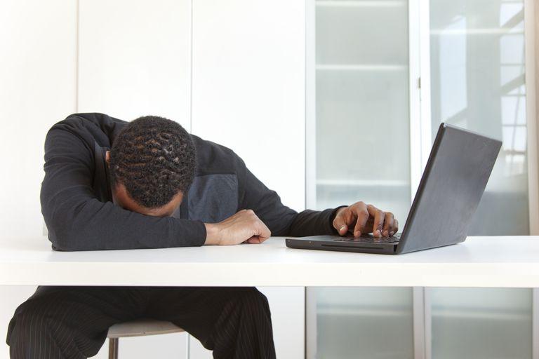 Tired Black businessman sleeping near laptop