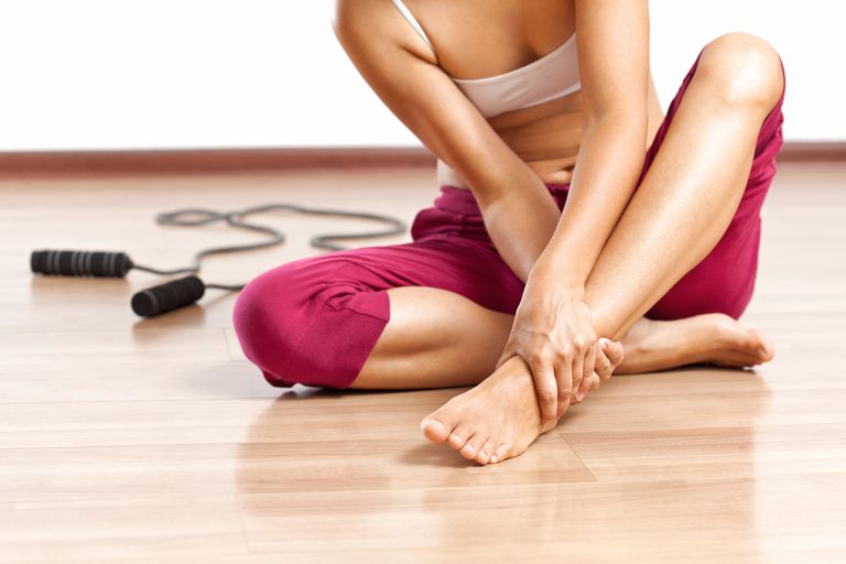 woman in fitness gear with sore foot