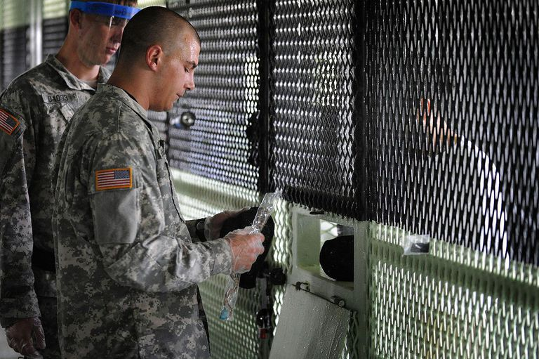 Army Spc. Anthony Berkowitz gives religious items to a detainee in Camp Delta, Joint Task Force Guantanamo, July 7, 2010. Berkowitz is a chaplain's assistant responsible for providing a wide variety of religious items, such as prayer rugs, caps and beads.