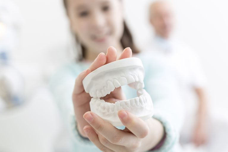 woman holding tooth model