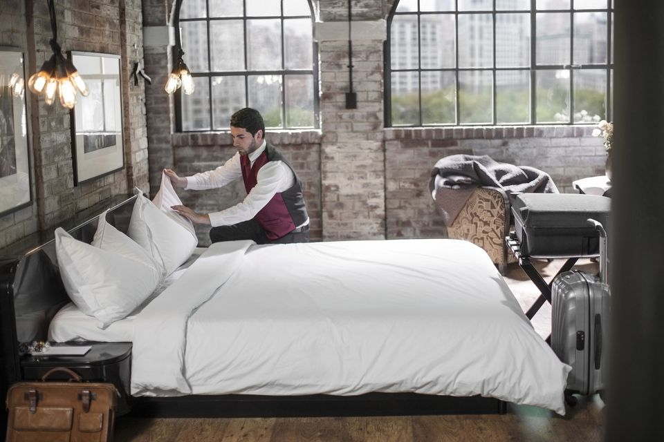 Housekeeper in hotel room, making the bed