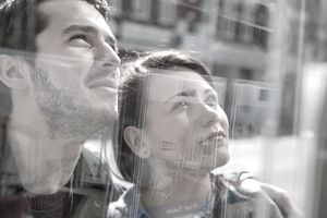 young couple looking in window at real estate advertisements