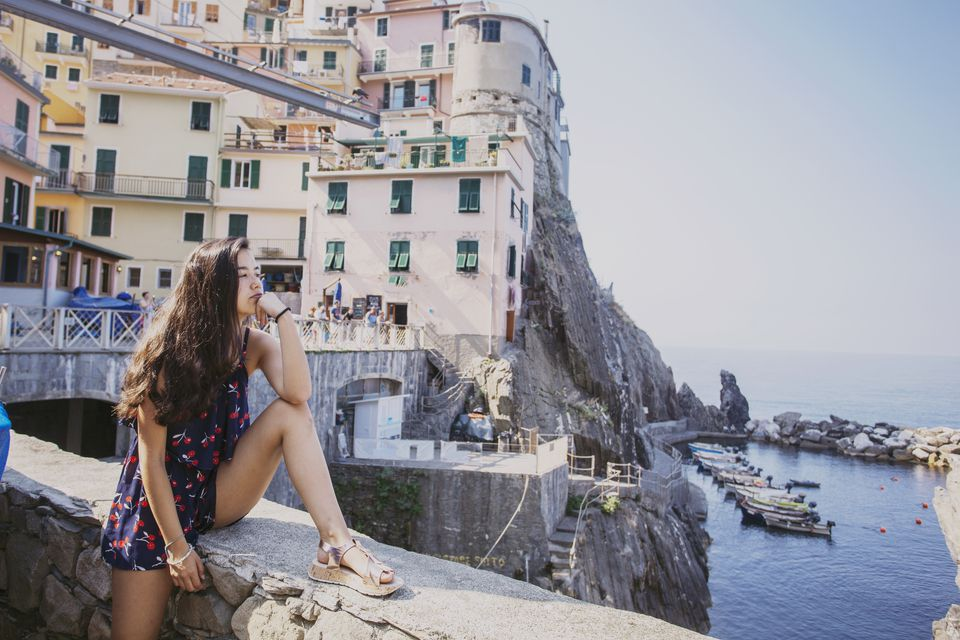 Teenager sitting looking at Manarola, Cinque Terre, Italy