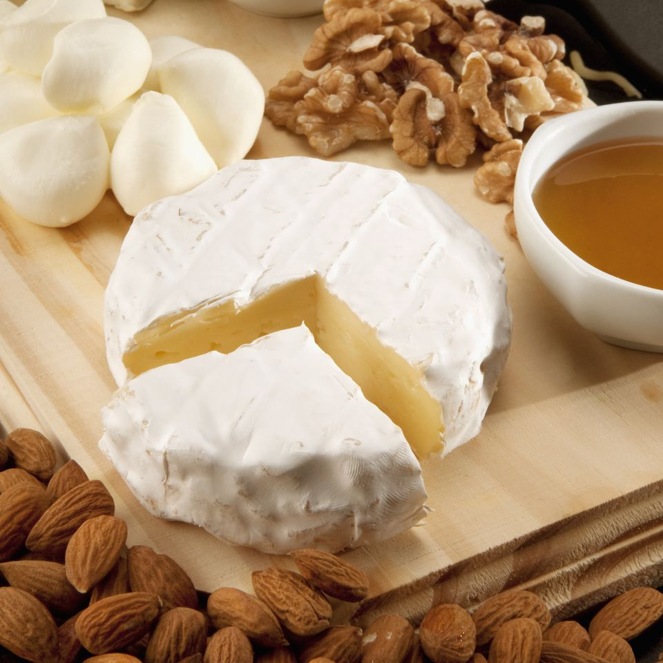 High angle view of assorted cheeses served with dry fruits
