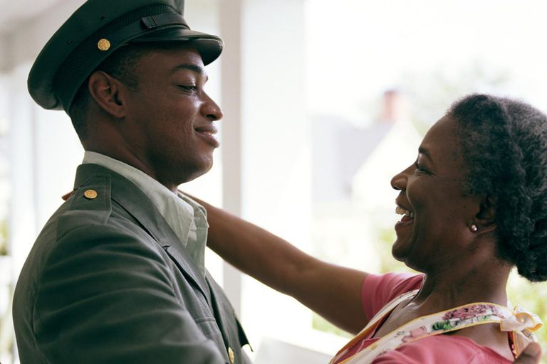 Senior woman in apron smiling at son in military uniform, side view