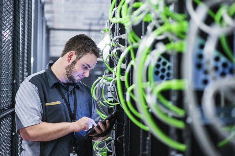 Technician using digital tablet in server room