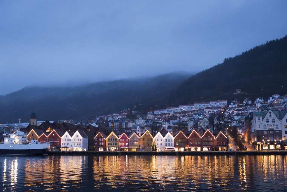 Colourful wooden buildings along Bryggen lit up in the morning with foggy mountain background