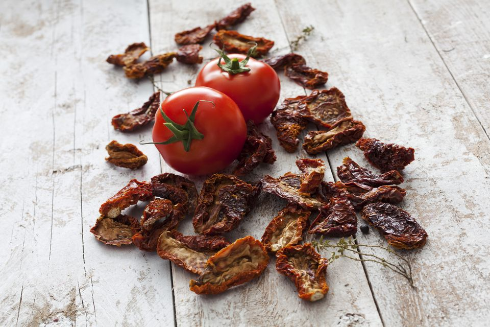 Dried and fresh tomatoes on wood