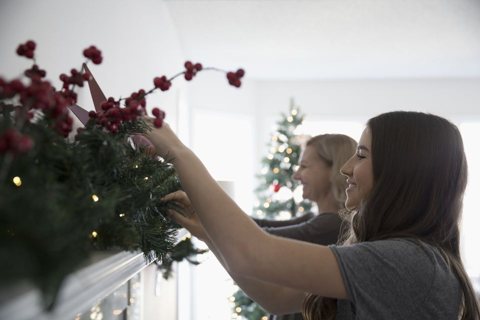 Mother and daughter decorating, hanging garland on fireplace mantle in living room