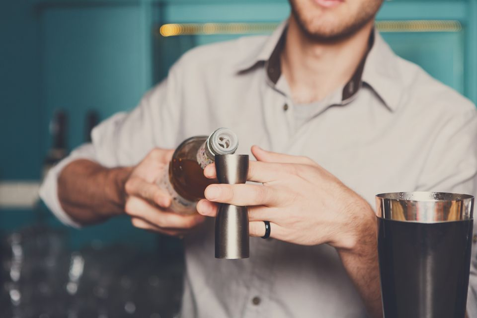 Bartender measuring a cocktail using a jigger.