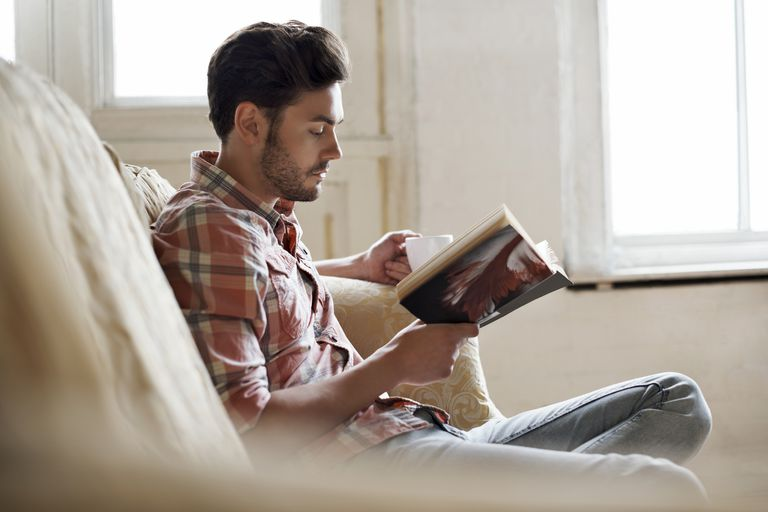 Man sitting on sofa reading a book in a cozy loft apartment