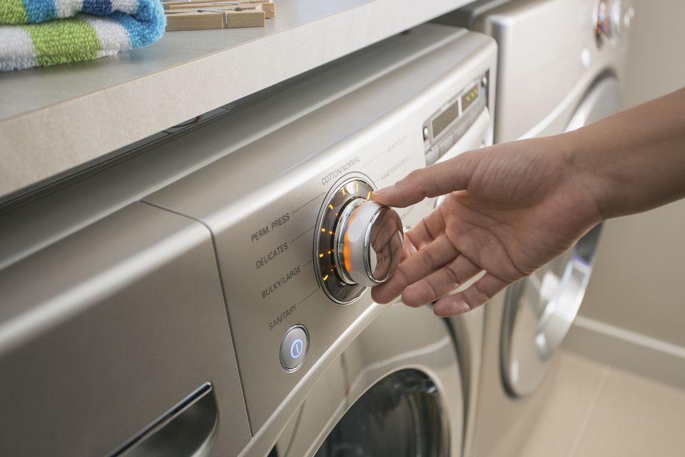Hand turning dial on washing machine