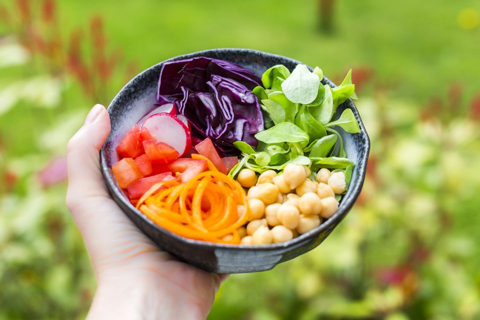 Rainbow salad in a bowl with chickpeas, tomatoes, carrots, red cabbage, red radishes, lettuce