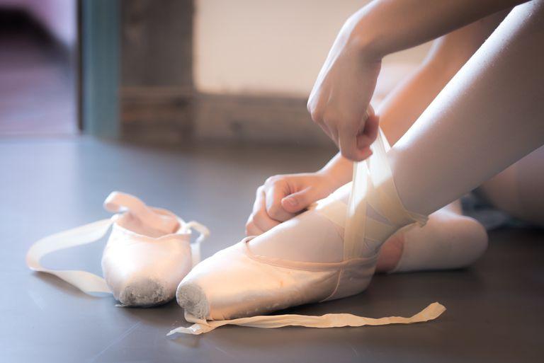 A ballet dancer laces her pointe shoes