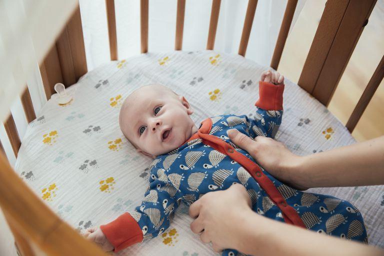 Mother putting her newborn baby boy into bassinet