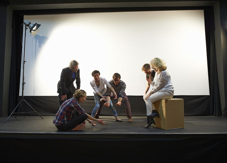Community theatre group rehearse on stage.