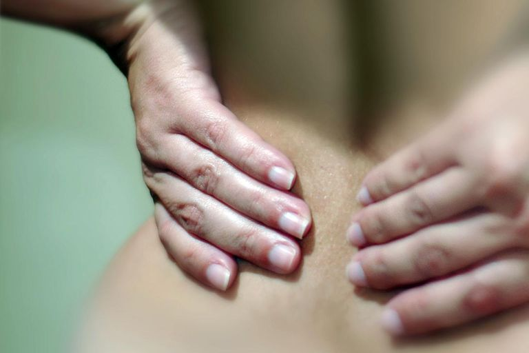 Close up of a woman's hands pressing against her lower back suggesting pain.