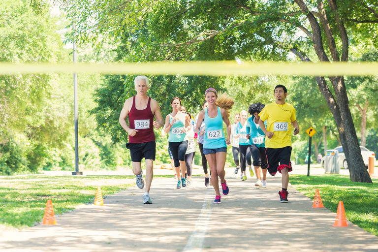 Diverse runners racing excitedly toward finish line during marathon