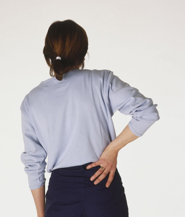 Woman rubbing the base of her spine, rear view.