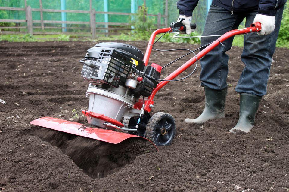 Person using garden tiller.