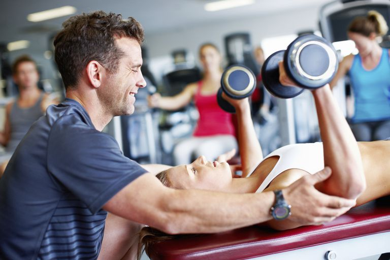 Woman lifting weights gym personal trainer