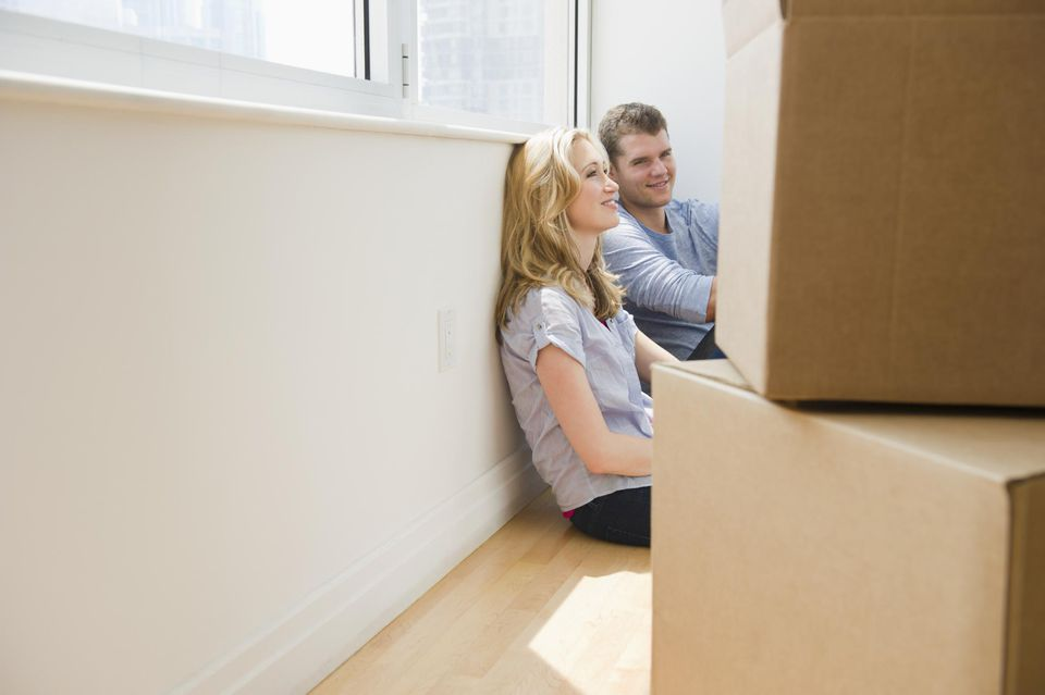 Couple relaxing with moving boxes in new apartment