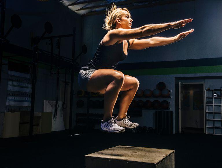 Woman jumping onto box
